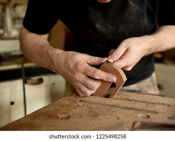 luthier modifies the head of a classical guitar.
