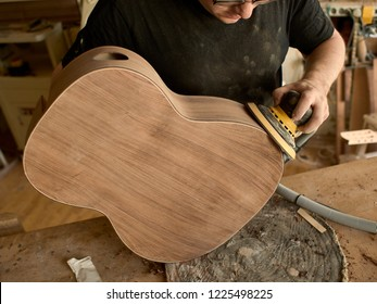 luthier polishes the body of a classical guitar.