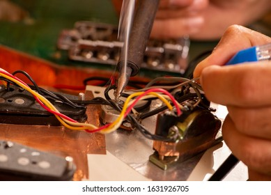 luthier soldering a guitar wire in his workshop