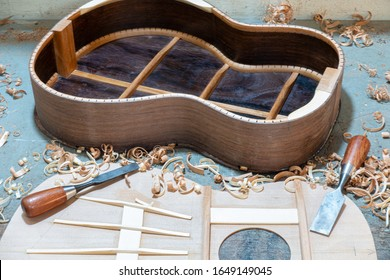 Luthier workbench with tools and an acoustic guitar under construction