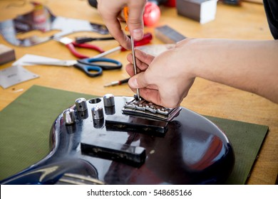 Luthier working on a guitar in his workshop