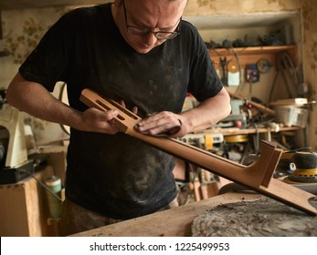 luthier is working on the neck of a classical guitar.