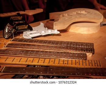 A luthier's desk with parts of an electric guitar being assembled.