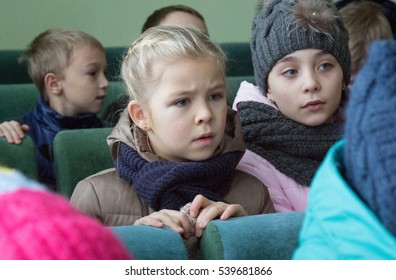 LUTSK, UKRAINE - 02 December 2016: Caucasian children sitting at chair during trip to police department. Shallow depth of field.