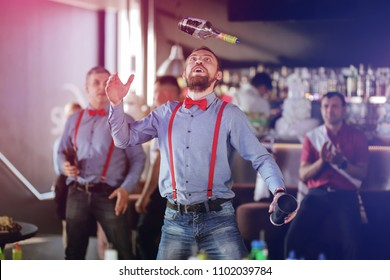 Lutsk, Ukraine, April 29, 2018: Bartender doing flair inside american bar - Barman at work performing freestyle - Focus on man face - Bartending, vacation, tropical