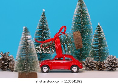Lutsk, Ukraine, December 17, 2017. Car with a Christmas tree in a snow-covered miniature evergreen forest.
