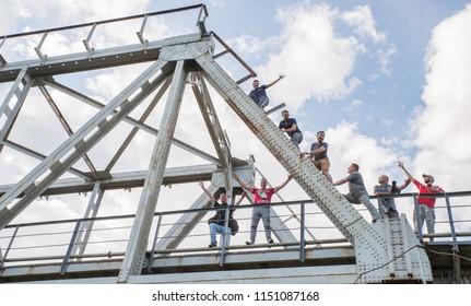 Lutsk, Ukraine, July 17, 2017:People on top of a metal construction of a railway bridge against a blue sky.