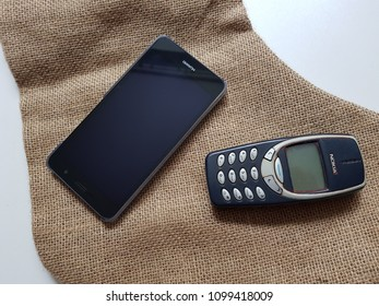 Lutsk, Ukraine, May 17, 2018: A modern smartphone and a old classic cell phone, difference concept