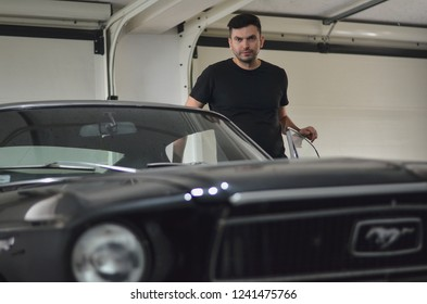 Lutsk, Ukraine - November 03, 2018: Man happy owner of a retro first generation Ford Mustang car. Selective focus.