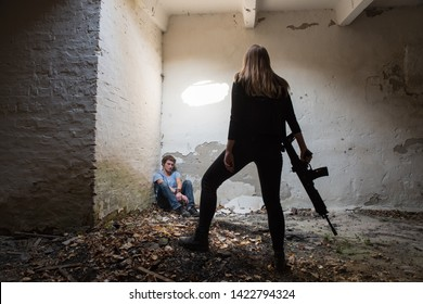 Lutsk. Ukraine. October 19, 2018; A girl with a gun guards a hostage in the basement of the ruins of a house.