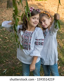 Lutsk. Ukraine. October 19, 2019; Little girls in embroidered shirts and wreaths on their heads in autumn willow branches.