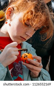 Lutsk, Volyn / Ukraine - April 20 2009: Girl with pysanka and tool for painting easter egg - pisachok at class. Shallow depth of field.