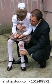 LUTSK, Volyn / UKRAINE - August 30 2009: Lutsk, Volyn / Ukraine - August 30 2009: Father hugging and calms little daughter in tattered pantyhose