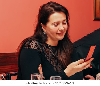 Lutsk, Volyn / Ukraine - February 06 2010: Woman typing text message on mobile phone in a cafe