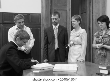 LUTSK, Volyn / UKRAINE - July 26 2009: Priest is signing significant document for wedding ceremony in church