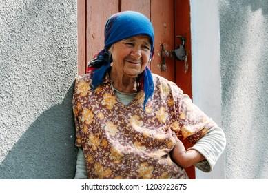 Lutsk, Volyn / Ukraine - July 29 2009: Old woman posing next to door of his house