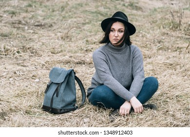 Lutsk, Volyn / Ukraine - March 07 2019: Stylish woman in hat with backpack sitting on the ground in spring