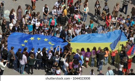 Lutsk, Volyn / Ukraine - May 17 2014: Young people holding a big flags of European Union and Ukraine during Europe Day