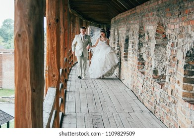 Lutsk, Volyn / Ukraine - May 24 2008: Young bride and groom walking holding hands in old castle