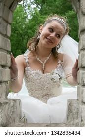 Lutsk, Volyn / Ukraine - May 24 2008: Happy bride posing in window of brick wall in wedding walk