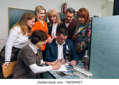 LUTSK, VOLYN / UKRAINE - November 11, 2017: Group of school teachers posing with microscope at laboratory