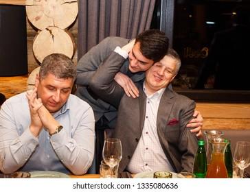 Lutsk, Volyn / Ukraine - November 17 2017: Uncle hugs his adult nephew in restaurant