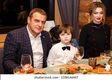 Lutsk, Volyn / Ukraine - November 17 2017: Man and little boy and woman in restaurant