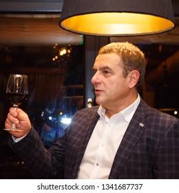 Lutsk, Volyn / Ukraine - November 17 2017: Man with a glass of red wine posing in restaurant