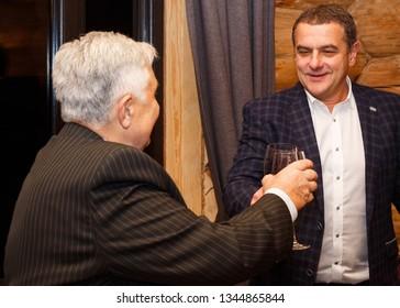 Lutsk, Volyn / Ukraine - November 17 2017: Senior father with adult son clicking wineglasses in restaurant