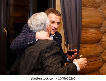 Lutsk, Volyn / Ukraine - November 17 2017: Adult son embraces his senior father in restaurant