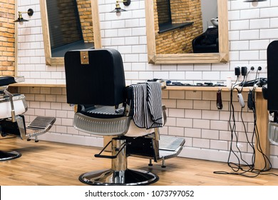 Lutsk, Volyn / Ukraine - November 29 2017: Empty barbershop with armchairs, barber equipment and mirrors on walls