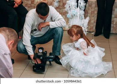 Lutsk, Volyn / Ukraine - October 12 2008: A little girl watches for man takes a video camera wedding in a restaurant