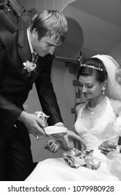 Lutsk, Volyn / Ukraine - October 12 2008: Groom with shoe and bride with money during wedding competitions in restaurant