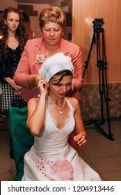Lutsk, Volyn / Ukraine - October 14 2008: Mother take off bride veil after wedding ceremony at restaurant