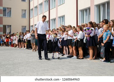 Lutsk, Volyn / Ukraine - September 01 2018: School Director and small schoolgirl with the bell during the ceremony of opening the new school