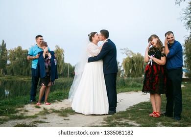 Lutsk, Volyn / Ukraine - September 16 2018: Funny portrait of newlywed couple kissing, bridesmaids and groomsmen hide eyes in park