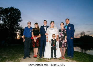Lutsk, Volyn / Ukraine - September 16 2018: Bride and groom posing with guests in evening at park