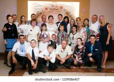 Lutsk, Volyn / Ukraine - September 16 2018: Groom and bride with guests posing in restaurant