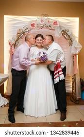 Lutsk, Volyn / Ukraine - September 16 2018: Two men kissing bride in cheek in restaurant
