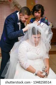Lutsk, Volyn / Ukraine - September 16 2018: Mother and groom take off bride veil after wedding