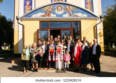 Lutsk, Volyn / Ukraine - September 30 2018: Groom and bride with guests posing next to church