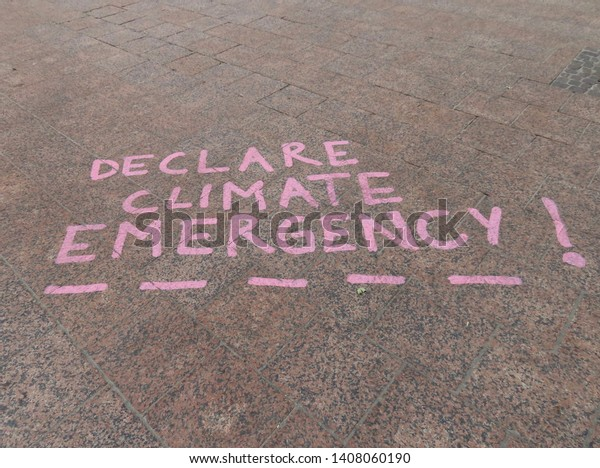 """Luxembourg city / Luxembourg - 05/23/2019: Writing on tiled street by students taking part in climate change protests in Luxembourg. Pink text on brown ground """"Declare climate emergency!"""""""