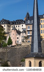 Luxembourg City. Luxembourg. 06.05.18. Ville de Luxembourg. The walls of the old town viewed from the Grund area of the city. The spire in the foreground is the church of St John Neimenster.