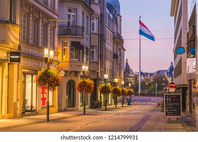 LUXEMBOURG CITY, LUXEMBOURG - 13TH OCTOBER 2018: A view along the Rue Philippe II at sunrise. The outside of buildings and shops can be seen. The Luxembourg Flag can be seen in the distance.