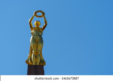 """LUXEMBOURG CITY, LUXEMBOURG - APRIL 18, 2019: Statue on top of the Monument of Remembrance (""""Golden Lady""""), sculpted by Claus Cito and inaugurated in 1923 showing Nike, the goddess of victory"""