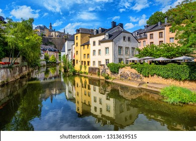 Luxembourg city, the capital of Grand Duchy of Luxembourg, view of the Old Town and Grund reflecting in Alzette river on a sunny summer day