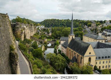 Luxembourg City, Luxembourg - September 24 2019: Chemin De la Corniche Fortified Wall on left, Neimenster Cultural Center and Church of Saint John in Grund on right and Alzette River in the middle