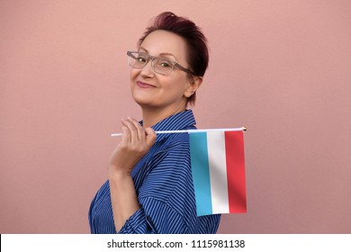 Luxembourg flag. Woman holding flag of Luxembourg. Nice portrait of middle aged lady 40 50 years old with a national flag over pink wall background outdoors.