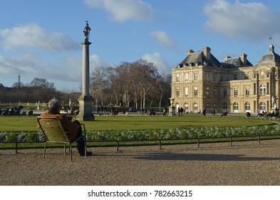 LUXEMBOURG GARDEN, PARIS/FRANCE - DECEMBER 2017: Old man seated in a chair, looking to people on the other side of a garden in Paris/France.