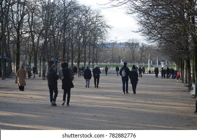 LUXEMBOURG GARDEN, PARIS/FRANCE - DECEMBER 2017: Walkway of sand with trees along the way with people walking in the same direction, winter in Luxembourg garden. Paris/France.